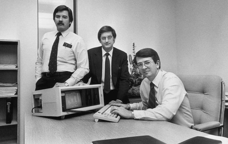 Três pessoas e um computador.